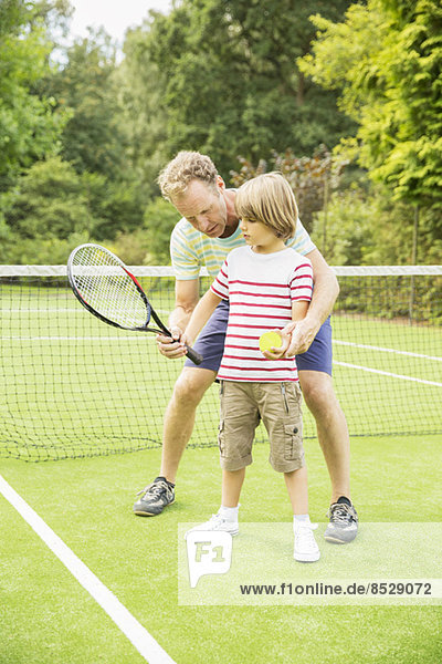 Vater lehrt den Sohn Tennis auf dem Rasen zu spielen.