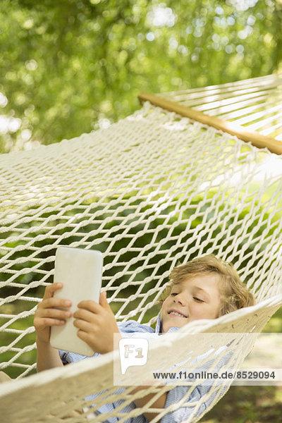 Junge mit digitalem Tablett in der Hängematte