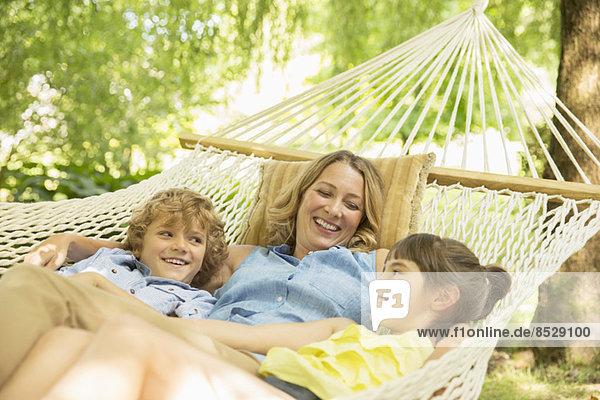 Mutter und Kinder entspannen gemeinsam in der Hängematte