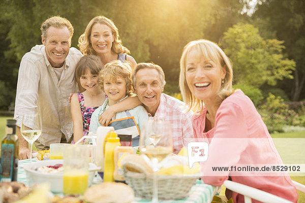 Mehrgenerationen-Familie am Tisch im Hinterhof
