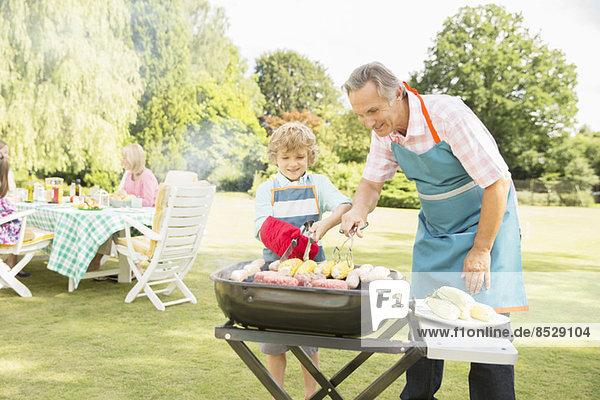 Großvater und Enkel beim Grillen von Fleisch und Mais auf dem Grill