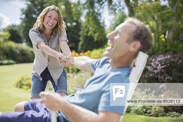 Frau zieht Freund aus dem Stuhl im Hinterhof
