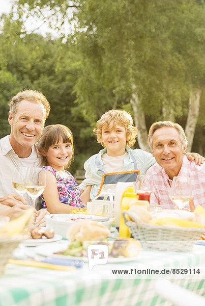 Mehrgenerationen-Familienessen am Tisch im Hinterhof