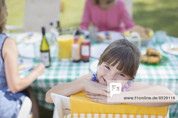 Mädchen lächelt bei Tisch im Hinterhof