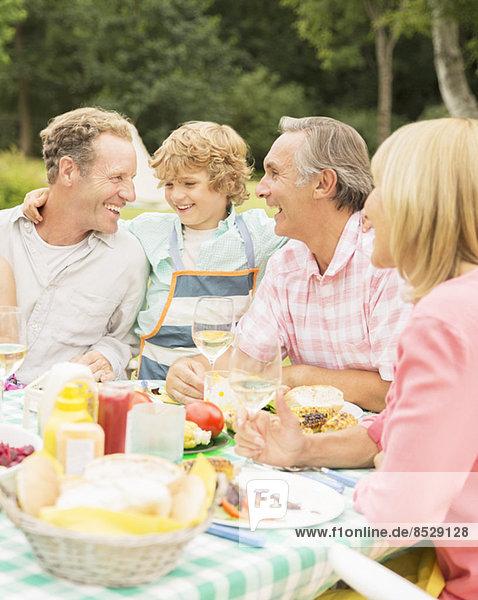 Familie genießt Mittagessen am Tisch im Hinterhof
