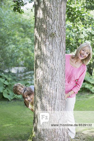 Großmutter und Enkelkinder blicken hinter den Baum