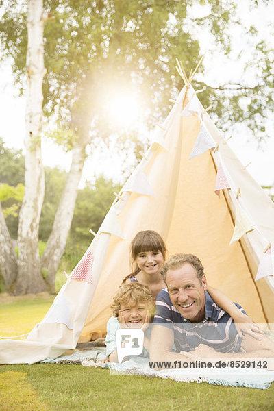 Vater und Kinder entspannen im Tipi im Hinterhof