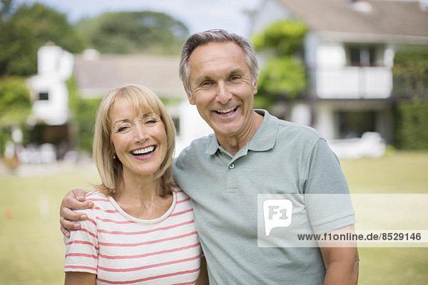 Lächelndes Seniorenpaar umarmt sich im Freien