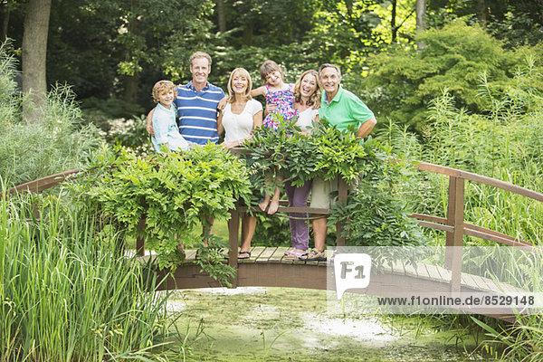 Mehrgenerationen-Familie auf Holzsteg über dem Teich stehend