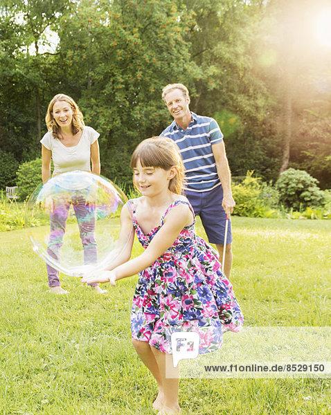 Familienspiel mit Blasen im Garten
