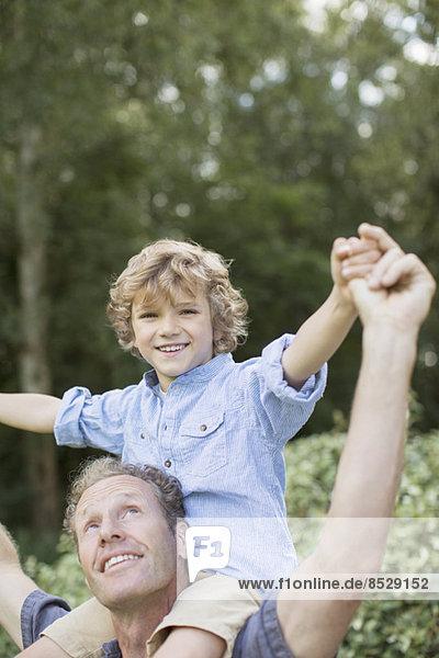 Vater trägt Sohn auf Schultern im Freien
