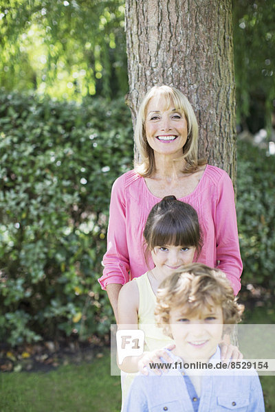Grandmother and grandchildren smiling outdoors