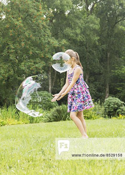 Mädchen spielt mit Blasen im Hinterhof