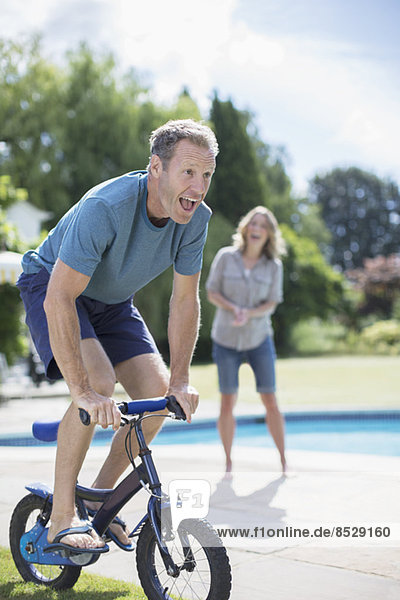 Man riding small bicycle at poolside