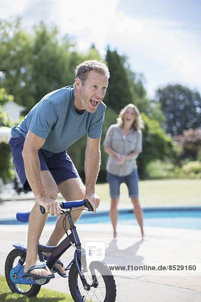 Mann mit kleinem Fahrrad am Pool