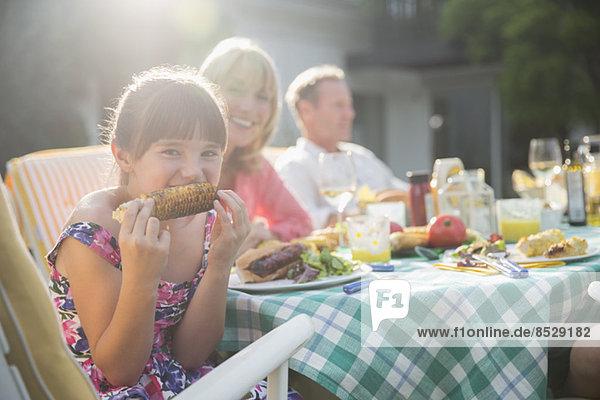 Mädchen essen Maiskolben bei Tisch im Hinterhof