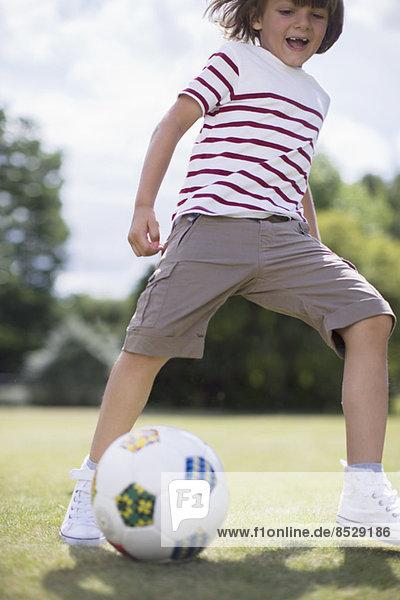 Junge spielt Fußball im Freien