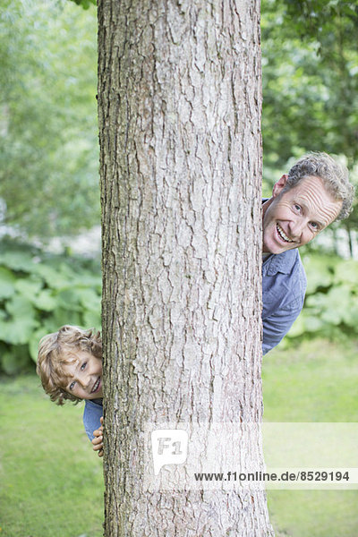 Vater und Sohn schauen von hinten auf den Baum.