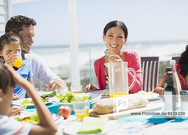 Familienessen auf der Terrasse mit Meer im Hintergrund