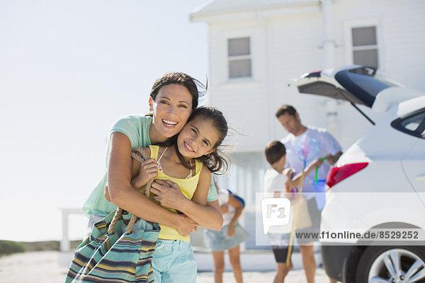 Mutter und Tochter umarmen sich vor dem Strandhaus