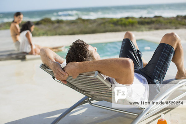 Mann entspannt im Liegestuhl am Pool