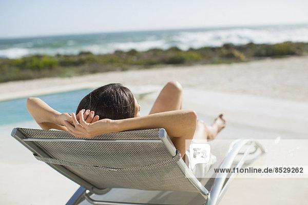 Frau beim Sonnenbaden auf dem Liegestuhl am Pool