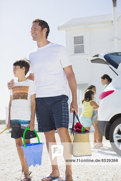 Vater und Sohn halten die Strandkleidung mit dem Auto.