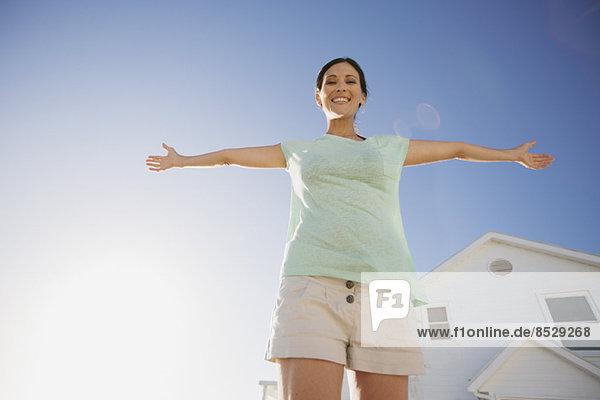 Frau lächelt mit ausgestreckten Armen gegen den blauen Himmel