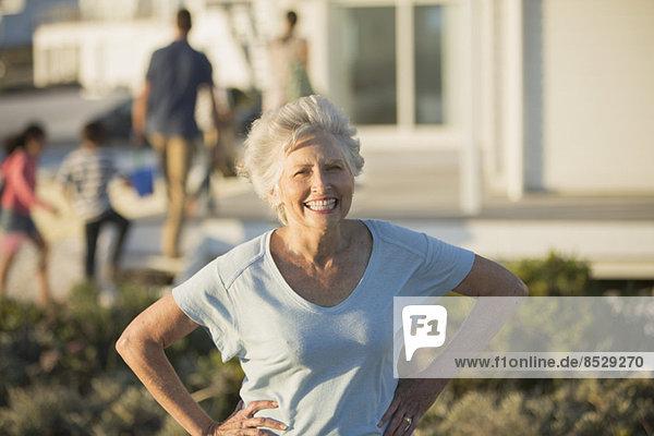 Seniorin lächelt mit Händen auf den Hüften im Freien