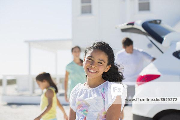 Mädchen lächelt in sonniger Einfahrt