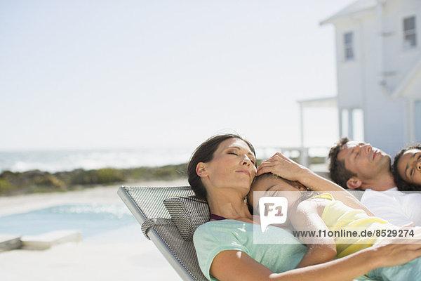 Familie schläft in Liegestühlen am Pool