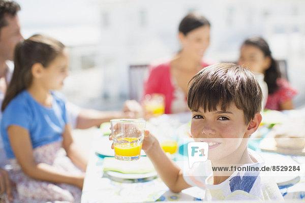 Junge trinkt Saft am Tisch auf der Sonnenterrasse