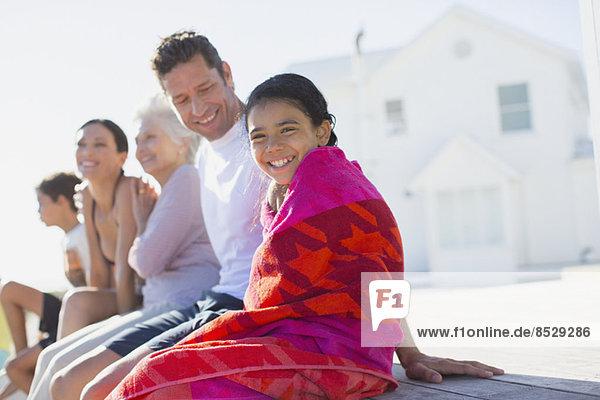 Mehrgenerationen-Familie vor dem Strandhaus sitzend