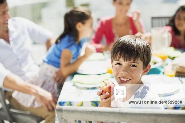 Junge isst Obst mit Familie am Tisch auf der Sonnenterrasse