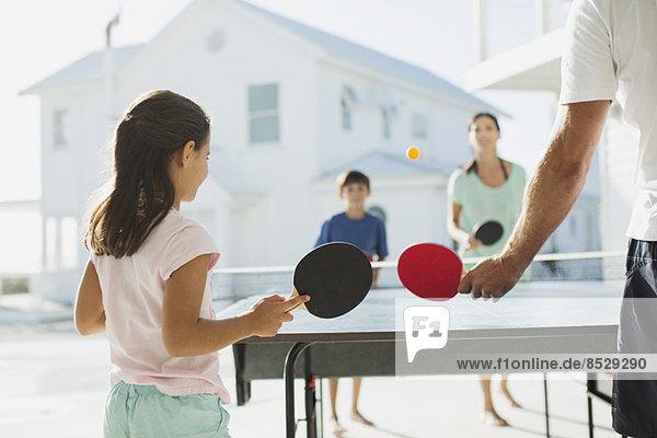 Familie beim gemeinsamen Tischtennisspielen im Freien