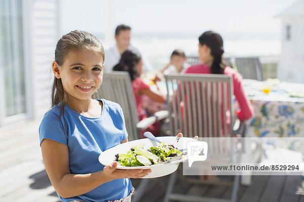 Mädchen mit Salat auf der Sonnenterrasse