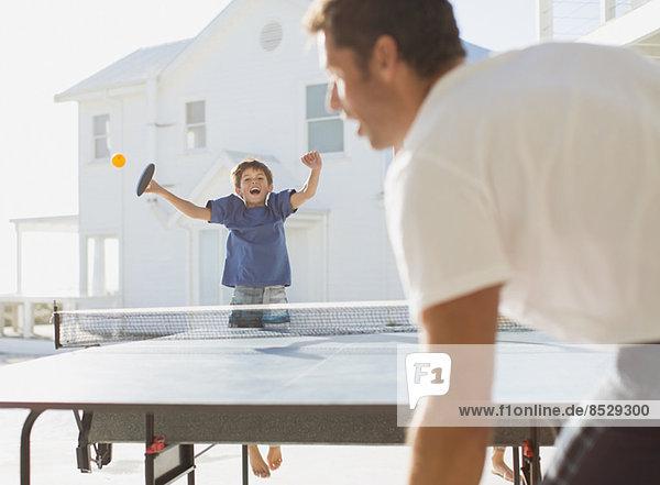 Vater und Sohn spielen Tischtennis im Freien