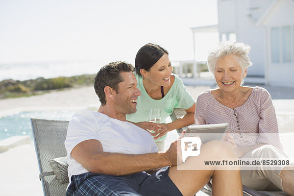 Familie mit digitalem Tablett am Pool