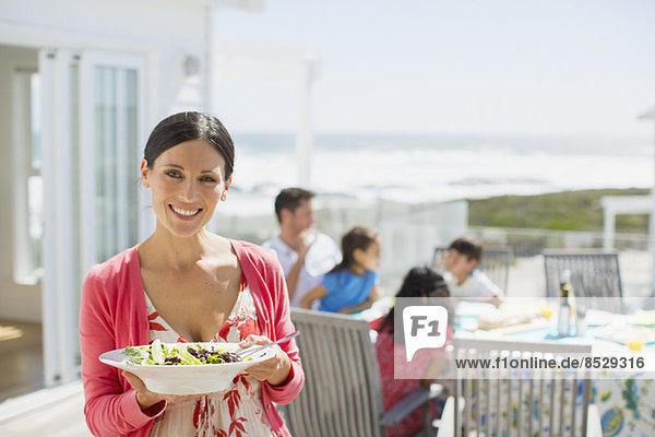Frau hält Salatschüssel auf sonniger Terrasse mit Blick auf den Ozean