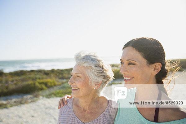 Mutter und Tochter lächeln am sonnigen Strand