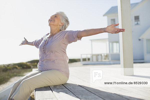 Seniorin mit ausgestreckten Armen auf Sonnendeck