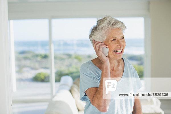 Seniorin am Handy im sonnigen Wohnzimmer