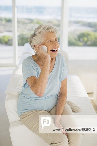 Seniorenfrau am Handy im Wohnzimmer