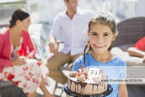 Mädchen mit Geburtstagskuchen lecken Lippen