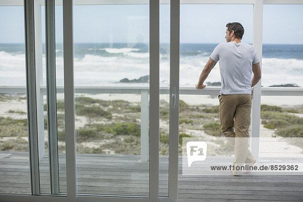 Mann blickt vom Deck auf den Ozean