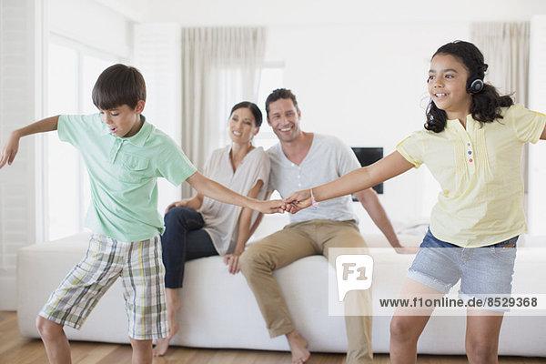 Eltern beobachten Tochter und Sohn beim Tanzen im Wohnzimmer