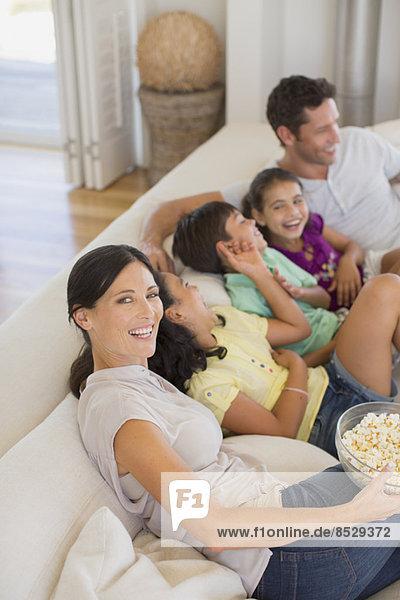 Familie lacht auf dem Sofa im Wohnzimmer