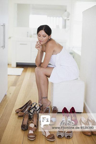 Frau wählt Schuhe im Schlafzimmer