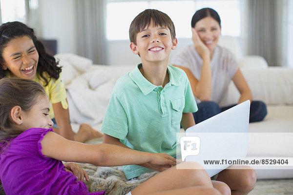 Familie mit Laptop auf Sofa im Wohnzimmer