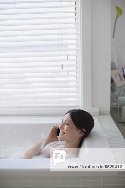 Frau beim Telefonieren in der Badewanne